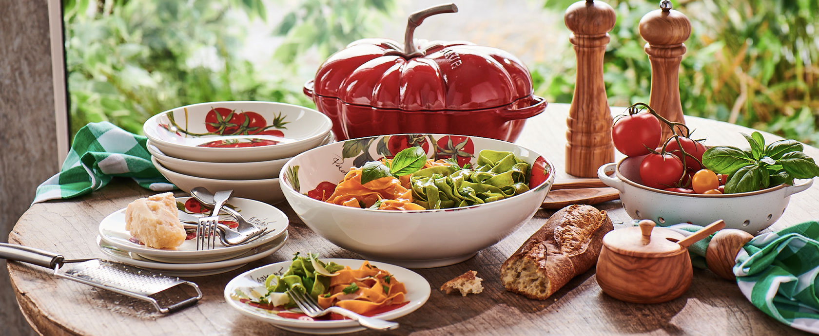 Summer table set with tomato dinnerware and Staub tomoto cocotte cookware.