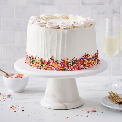 white birthday cake with rainbow colored sprinkles