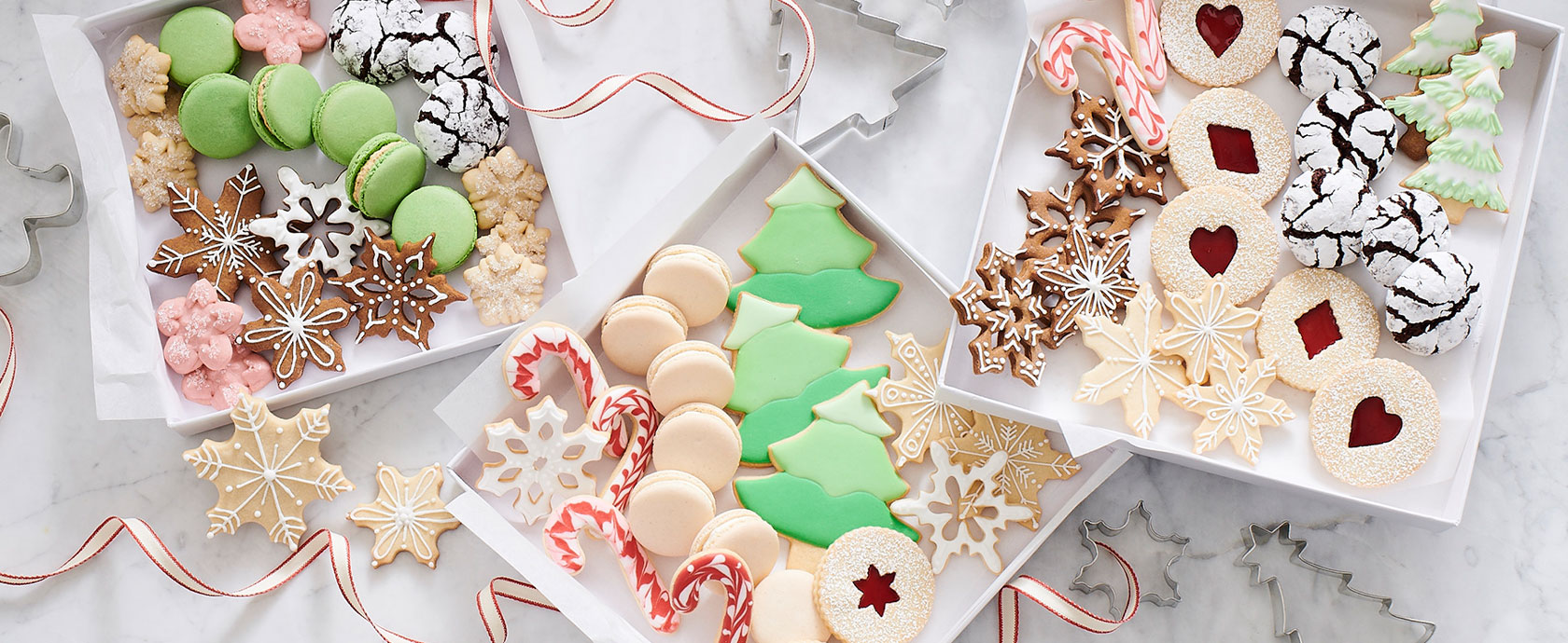decorated holiday cookies in white gift boxes
