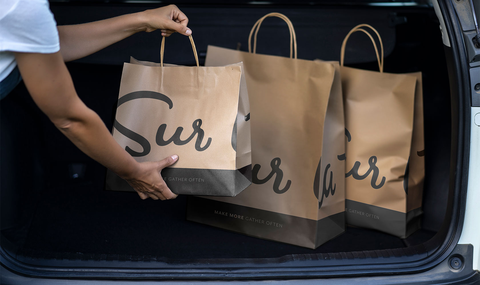 person unloading Sur La Table shopping bags from trunk of car