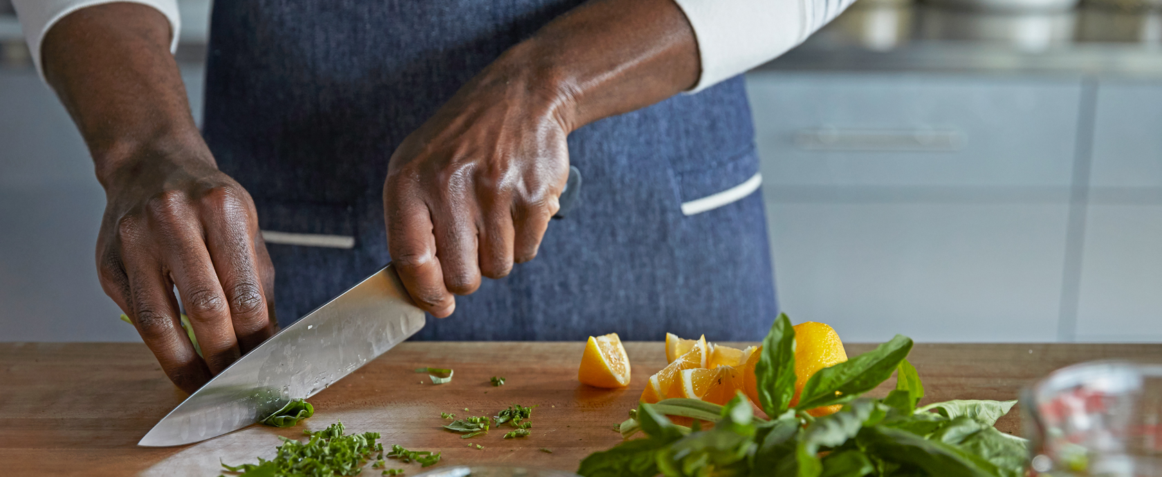 Chef chopping herbs on wooden counter
