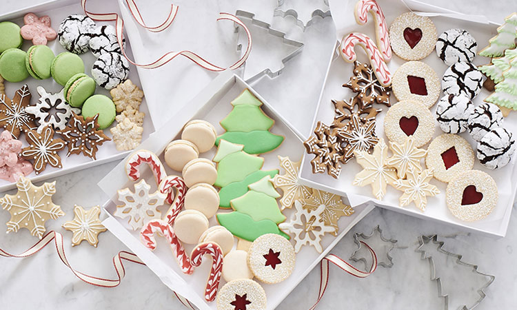 white trays of colorful holiday cookies.