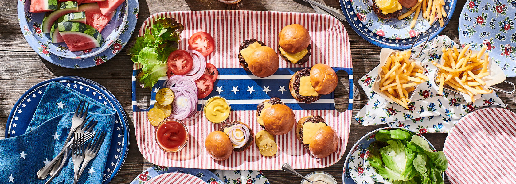 Summerhouse blue floral outdoor dinnerware on wooden table with stars and stripes platter with burgers