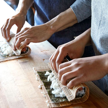 two chefs making sushi rolls in cooking class