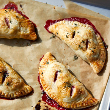 Small & Sweet: Berry Hand Pies on parchment paper