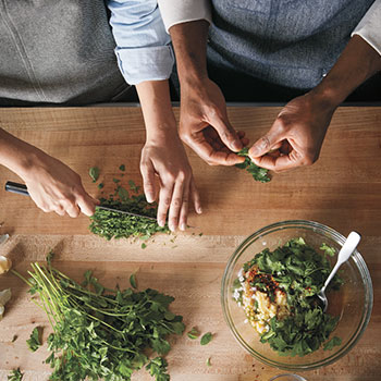 Two chefs chopping herbs