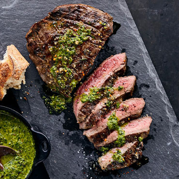 steak grilled and sliced with green sauce