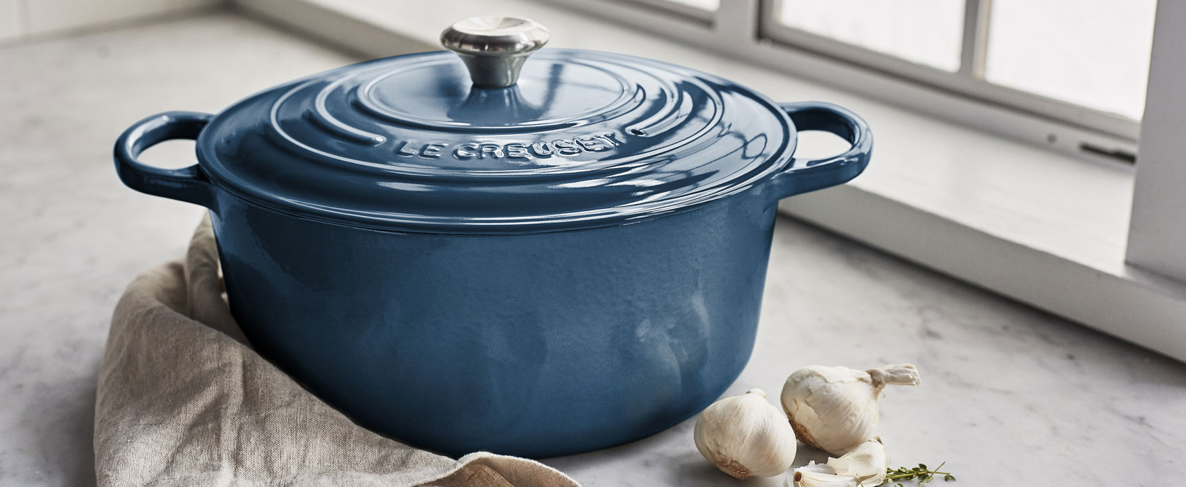 Le Creuset cookware in deep teal color