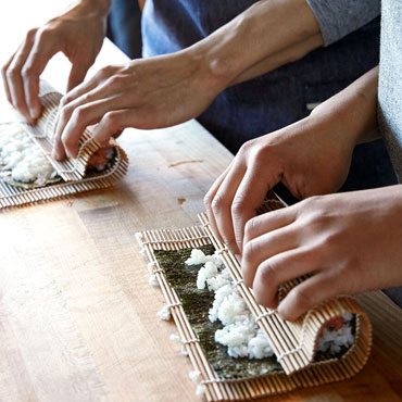 couple rolling sushi on cutting board