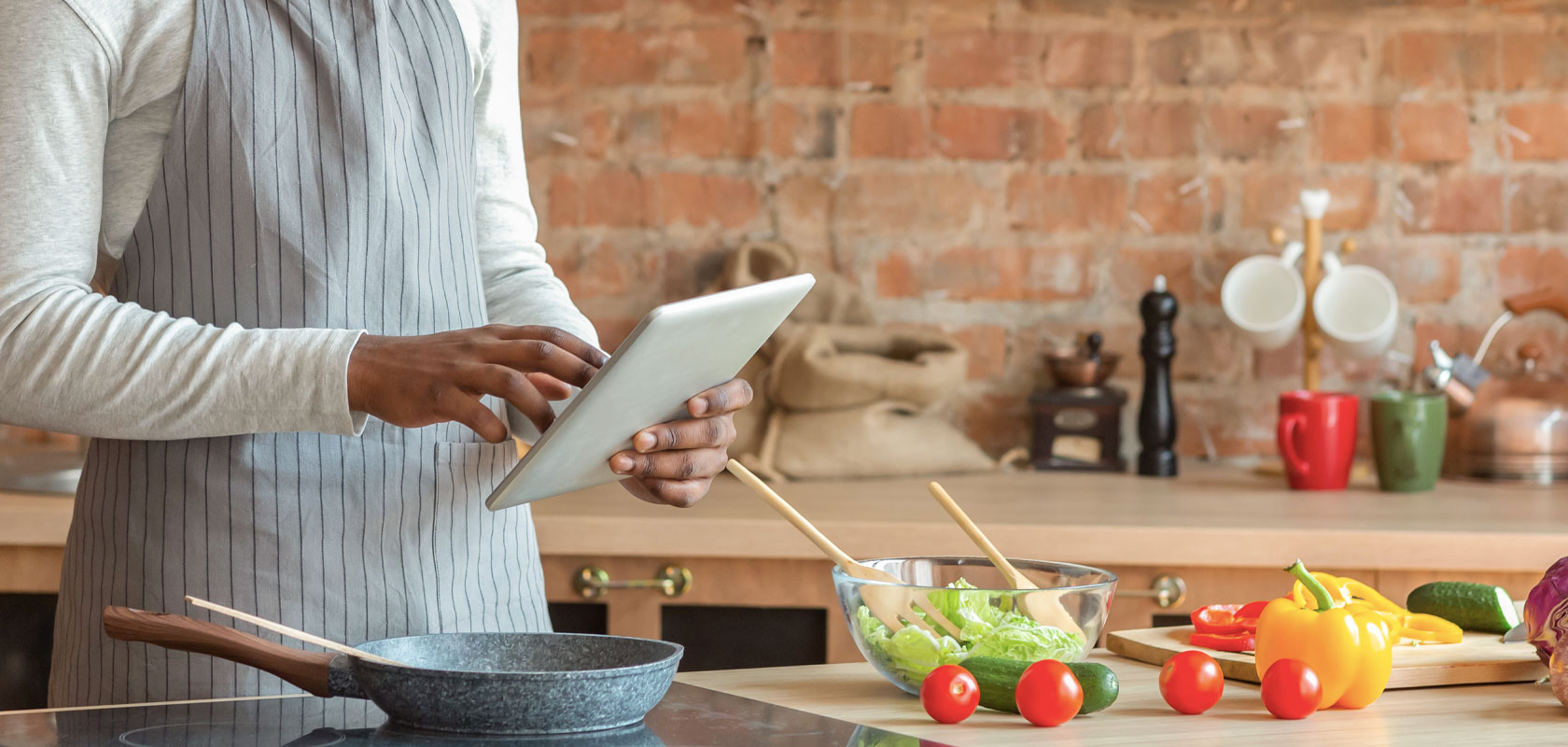 Sur La Table Online Culinary Institute, chef with gray striped apron and ipad in the kitchen