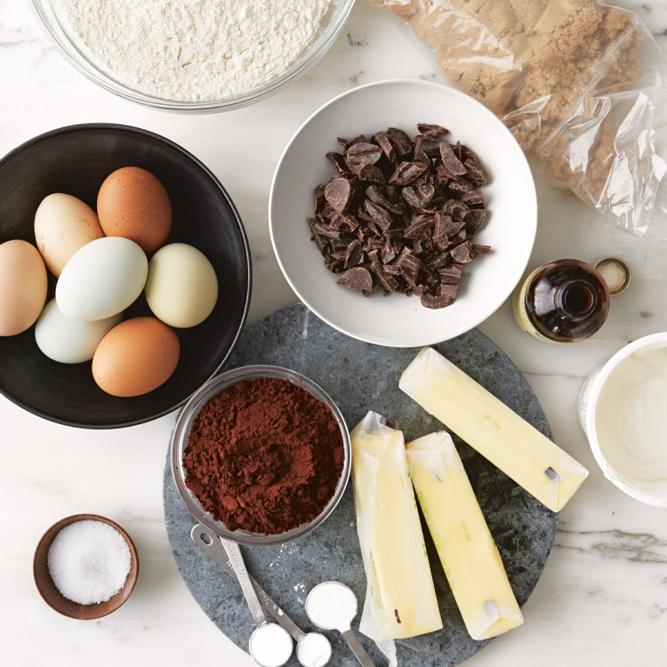 cake making ingredients of eggs, butter, vanilla and chocolate