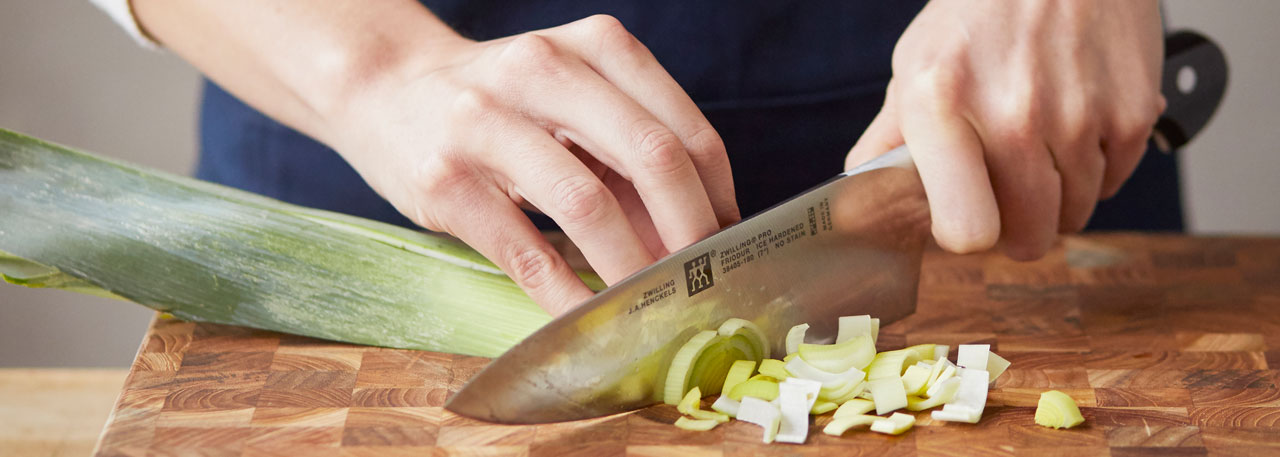 chef chopping leeks with Wustho knife