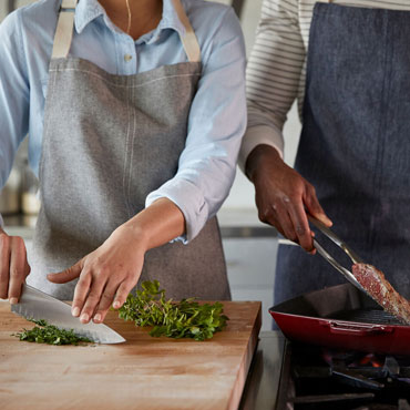 Chefs chopping herbs and searing steak