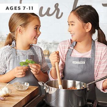 two girls cooking marinara sauce