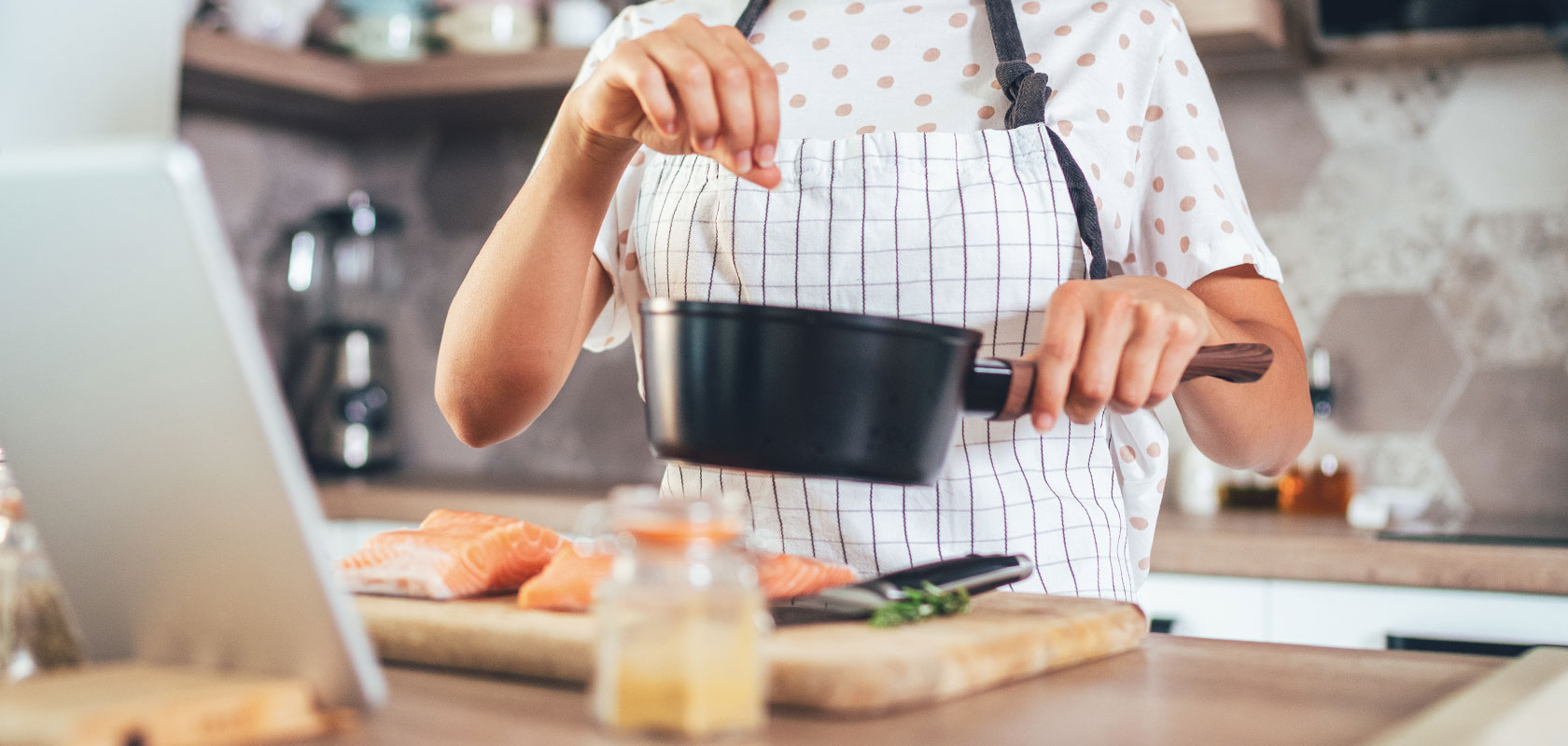 Sur La Table Online Culinary Institute, chef with white apron and ipad in the kitchen