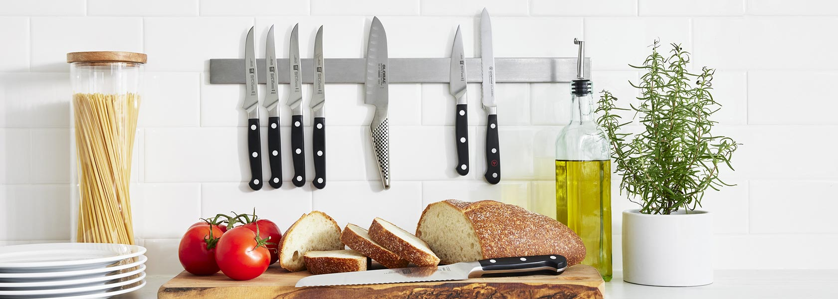 Chef's knives and paring knives on wooden cutting board