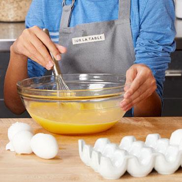 kids whisking eggs in glass bowl