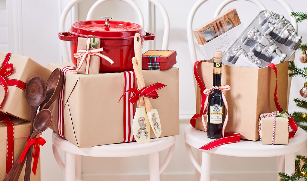 holiday gifts wrapped in brown paper with red ribbons