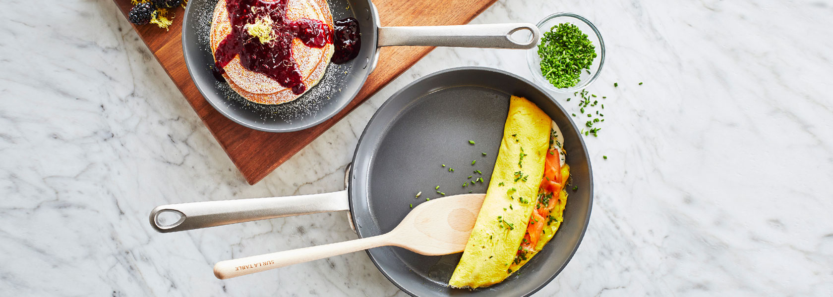 Skillets with pancakes and an omelette